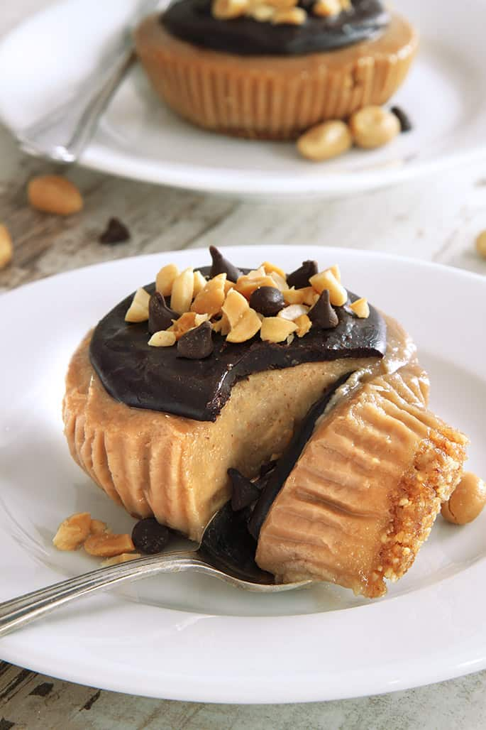 A peanut butter pie on a white plate with a metal spoon taking a piece of pie