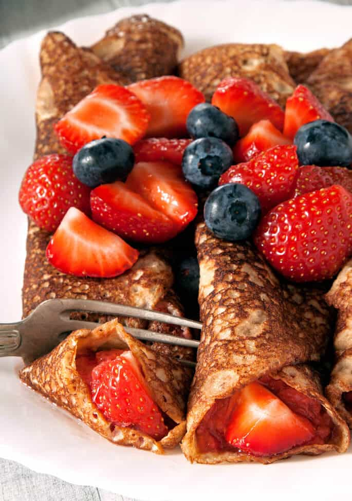 Close up of Swedish pancakes with fruit on top of them on a white plate being cut with a metal fork