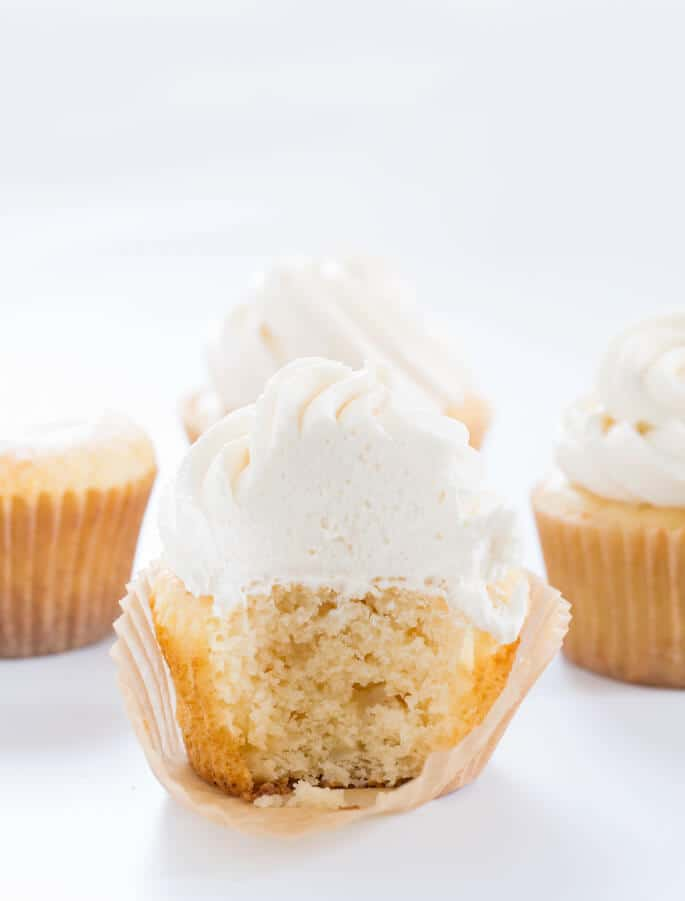 Inside view of vanilla cupcake with 3 other vanilla cupcakes in back on white surface