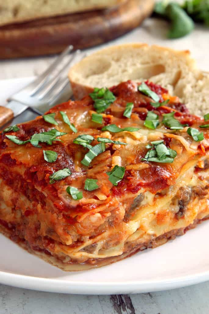 A close up side view of lasagna with herbs on top on a white plate