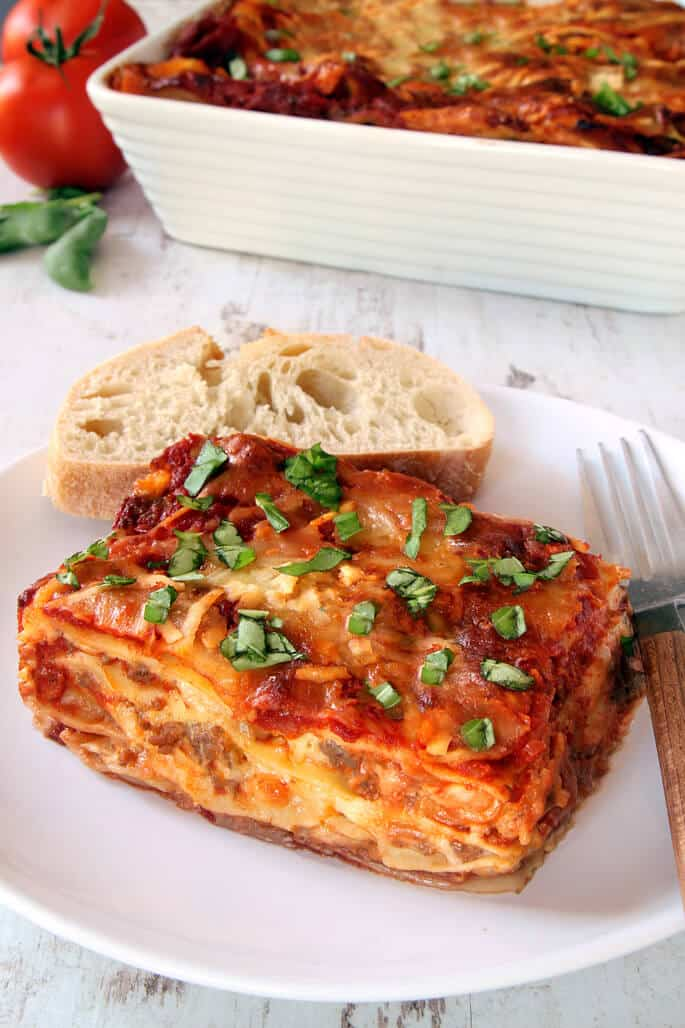 A close up of lasagna and a piece of bread on a white plate with a fork