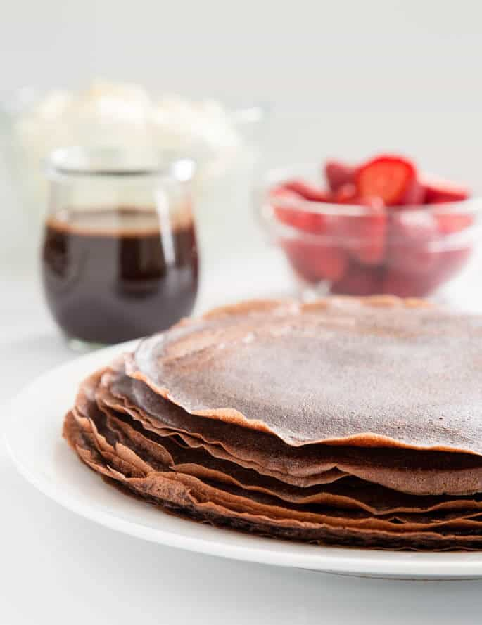 Learn how to make chocolate gluten free crêpes with this easy recipe. Fill with fresh whipped cream and drizzle with chocolate sauce for the perfect showstopper dessert!