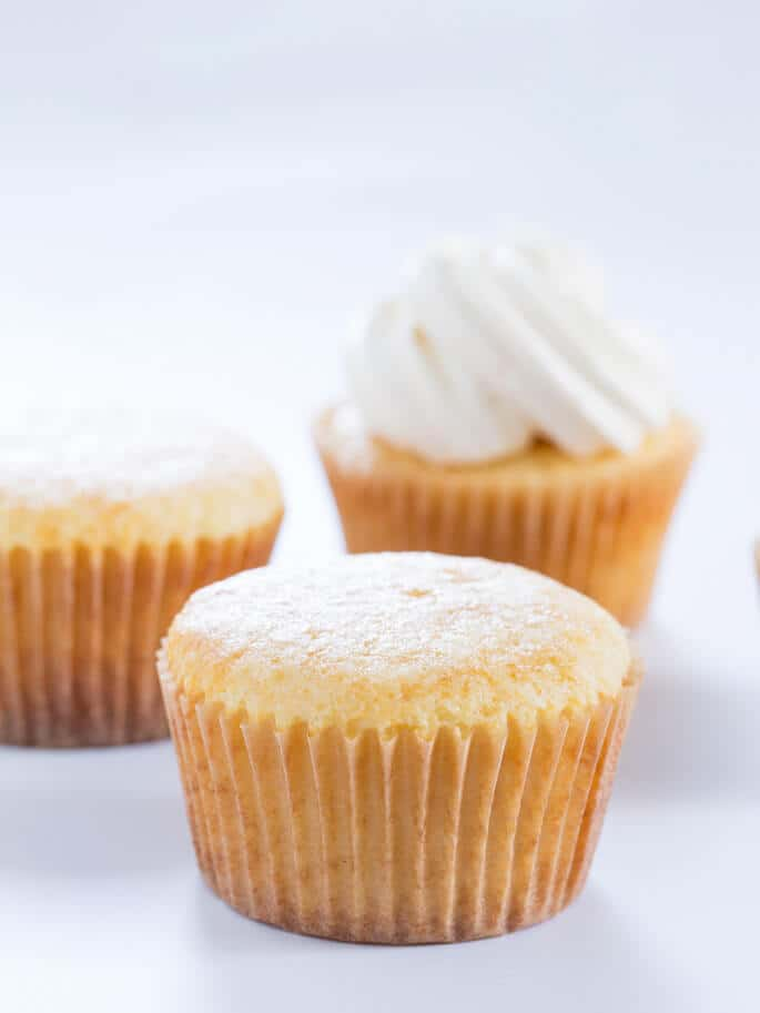 Close up of 3 vanilla cupcakes on white surface