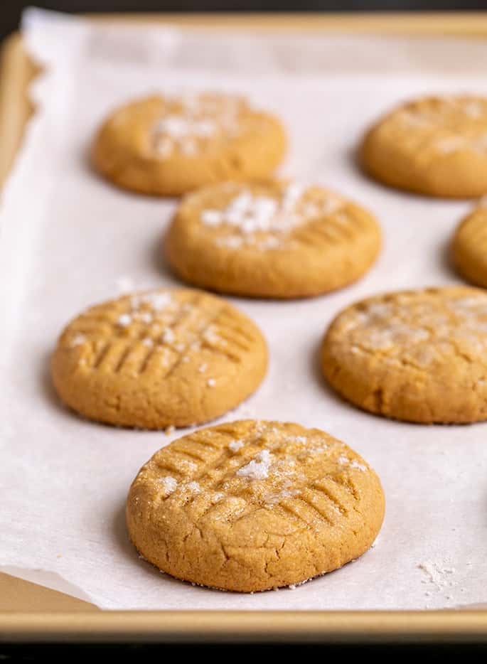 Baked peanut butter cookies on white paper on gold rimmed baking sheet