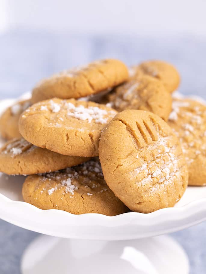 Pile of peanut butter cookies on small white cake plate on blue cloth