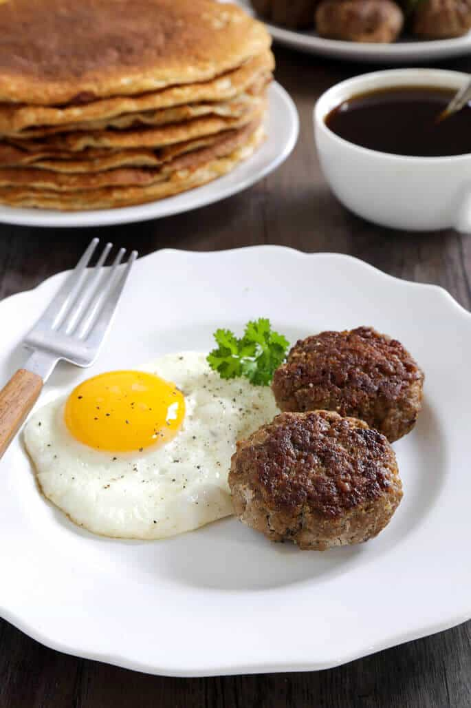 A white plate with a egg, 2 sausages and a fork