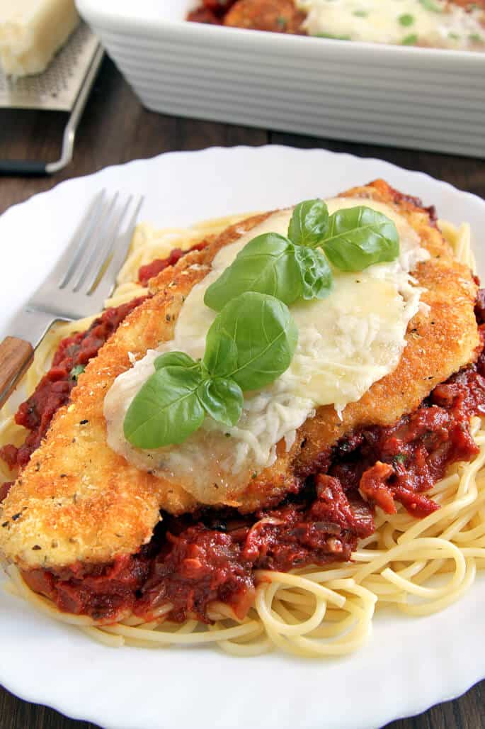 A close up of a spaghetti, red sauce and chicken parmesan on white plate