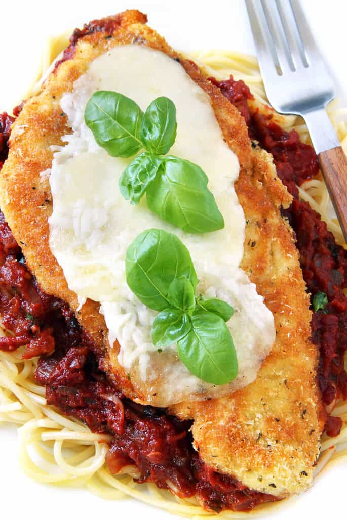 Zoomed in overhead view of spaghetti, red sauce and chicken parmesan