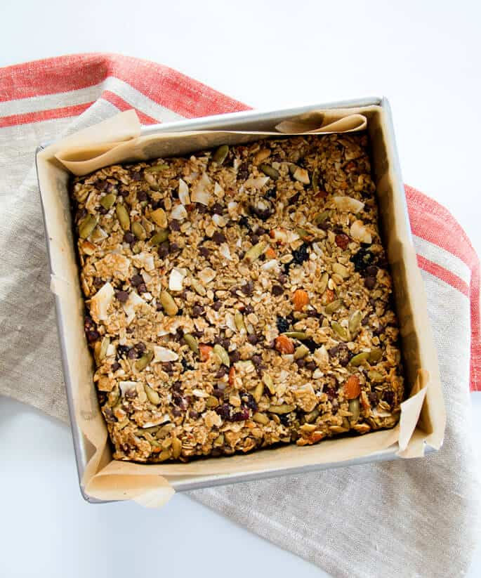 Overhead view of a baking tin with granola bars on a white surface with a gray towel that has red stripes