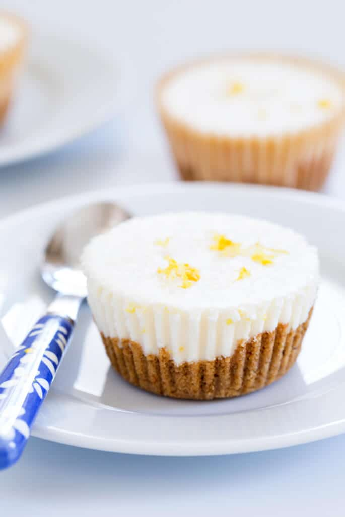Clear side view of lemon cheesecake on white plate with blue spoon