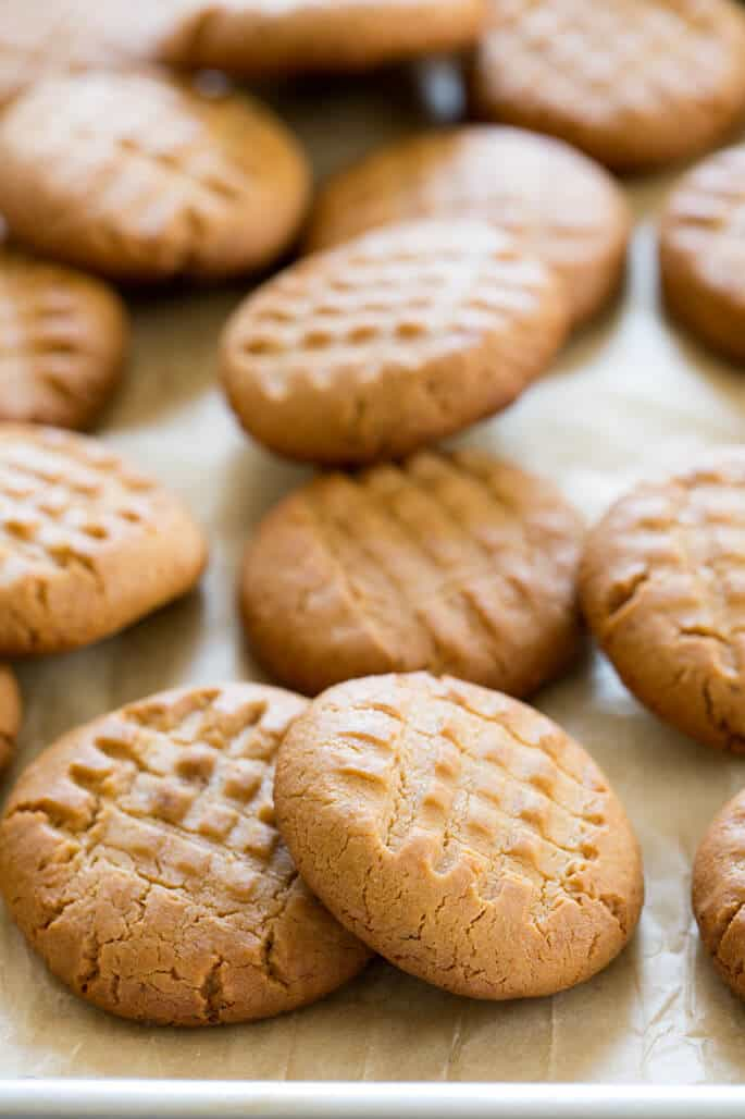 An overhead view of peanut butter cookies on beige paper