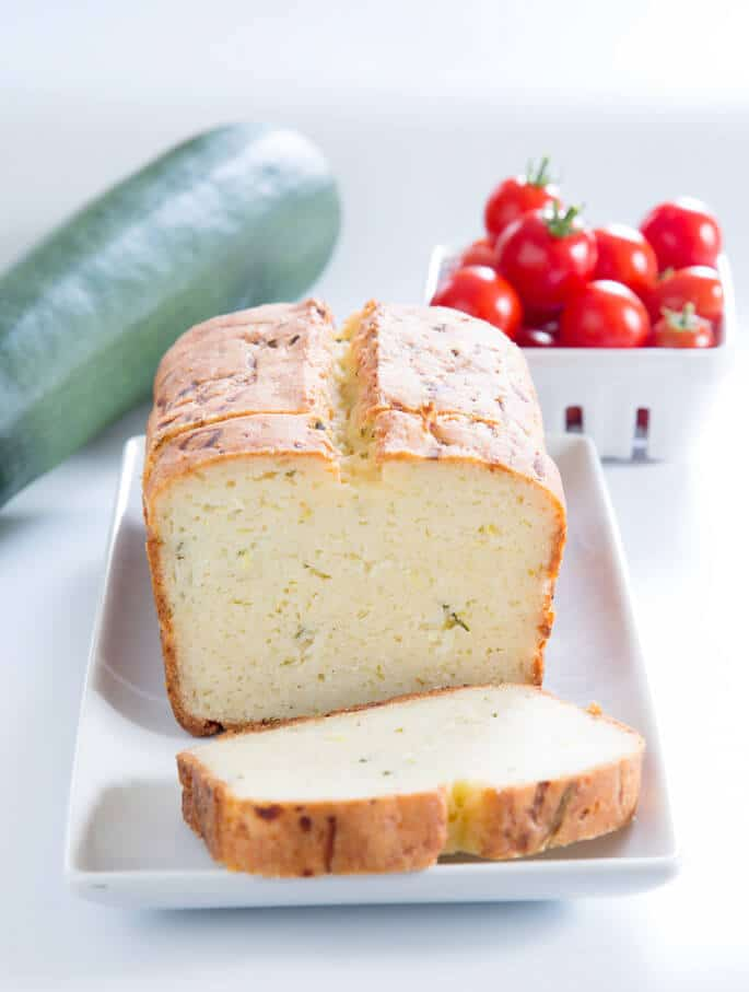 A close up of a loaf off zucchini bread with a slice on a white plate and a zucchini and bowl of tomatoes in back