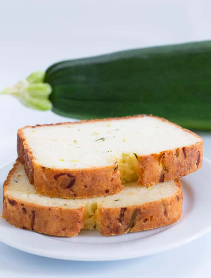A stack of 2 slices of zucchini bread on a white plate and a zucchini in the back