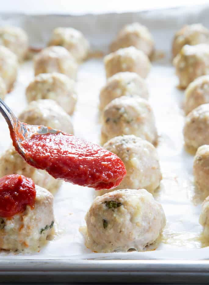 A close up a tray of chicken parm meatballs with red sauce being poured over them