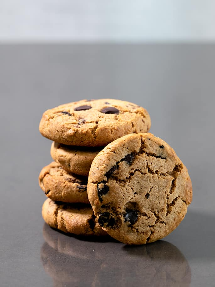 Four Paleo chocolate chip cookies in a stack with one on the side