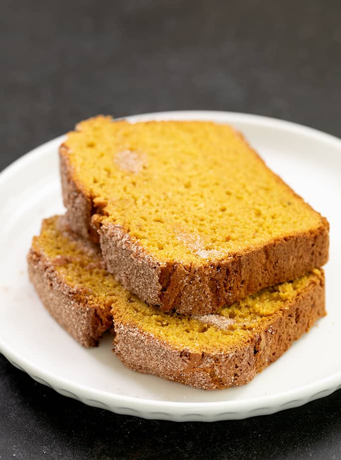 Two slices of pumpkin bread alone on a white plate