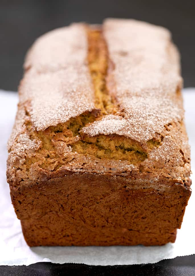 Whole baked pumpkin bread with cinnamon sugar on top sitting on white paper