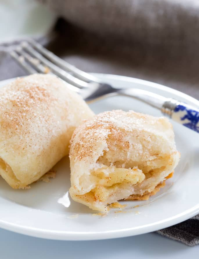 Close up of 2 apple dumplings in white plate with a blue fork