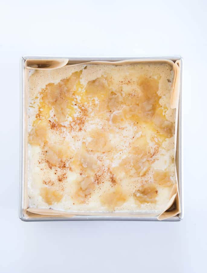 An overhead view of apple custard cake in metal tin on white surface