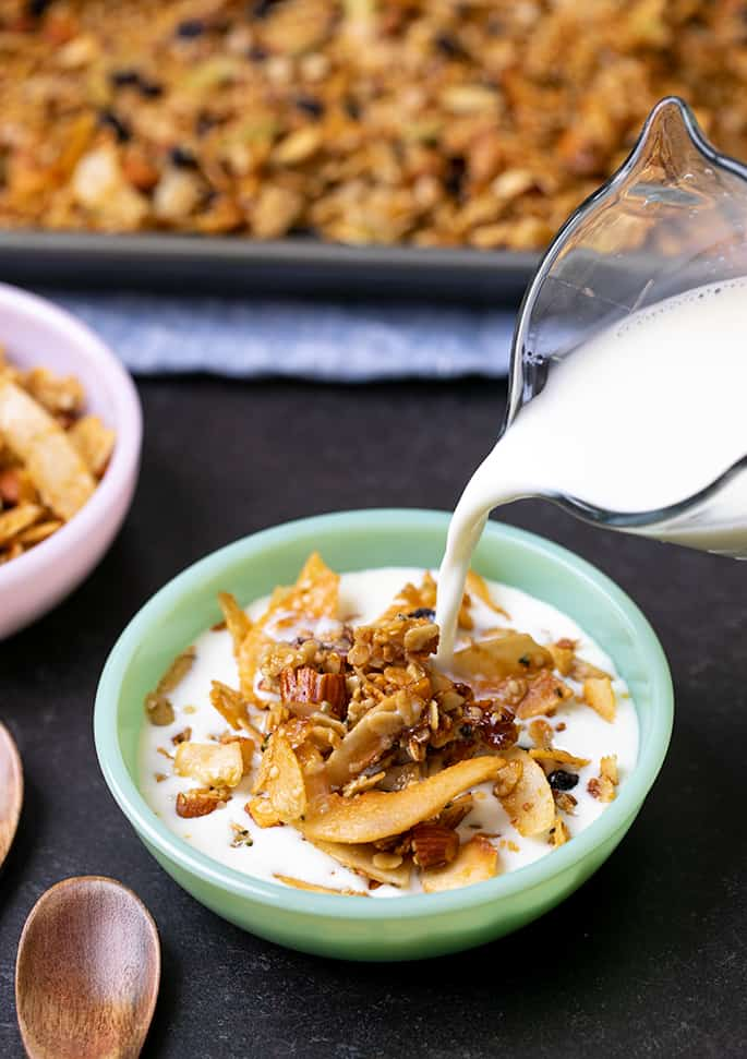 Milk pouring from glass jar into granola in small green bowl with spoons and pink bowl of granola