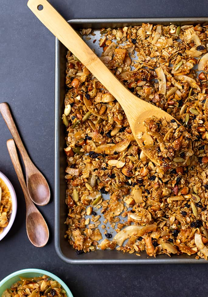 Overhead image of granola in rimmed baking sheet with wooden mixing spoon and individual wooden spoons on black surface