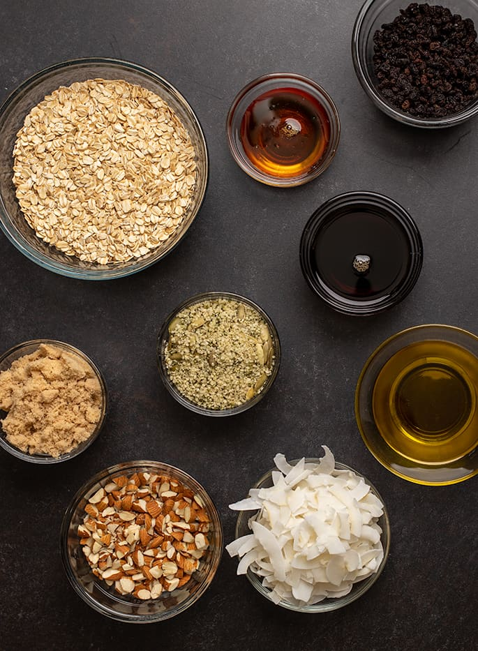 Overhead image of granola ingredients in round glass bowls
