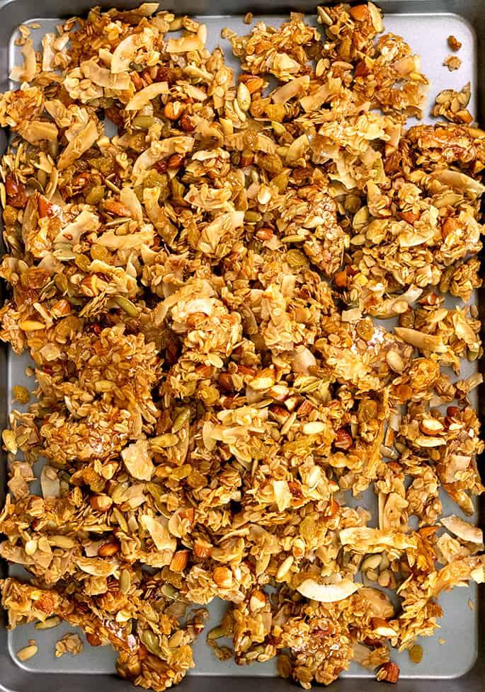 Overhead image of granola on nonstick half sheet pan, cooling