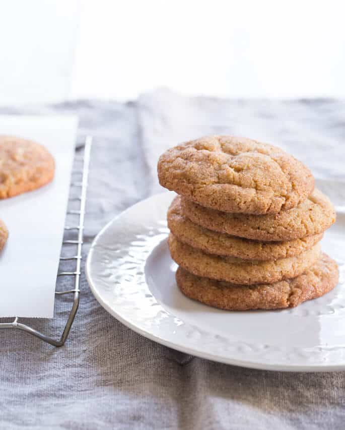 A close up of a stack of 5 snickerdoodle cookies on a white plate