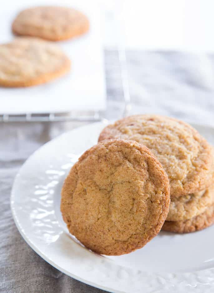 A stack of snickerdoodle cookies on a white plate with one cookie laying on the stack\'s side