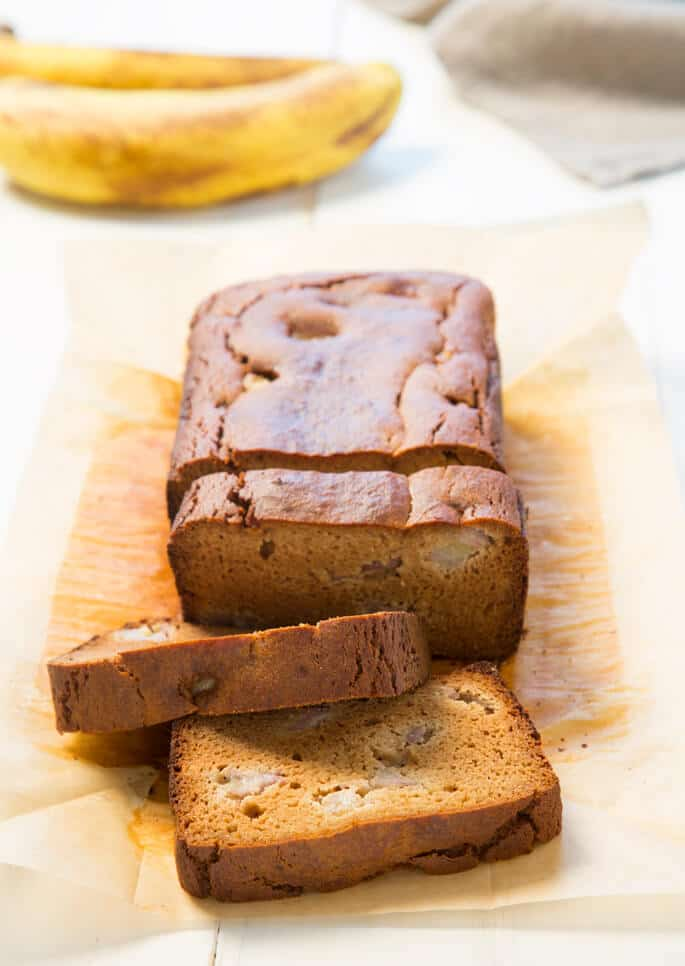 Close up of a loaf of banana bread with 3 slices on beige paper
