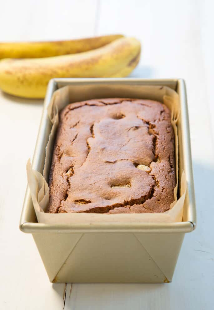 Overhead view of banana bread in baking tin on white surface