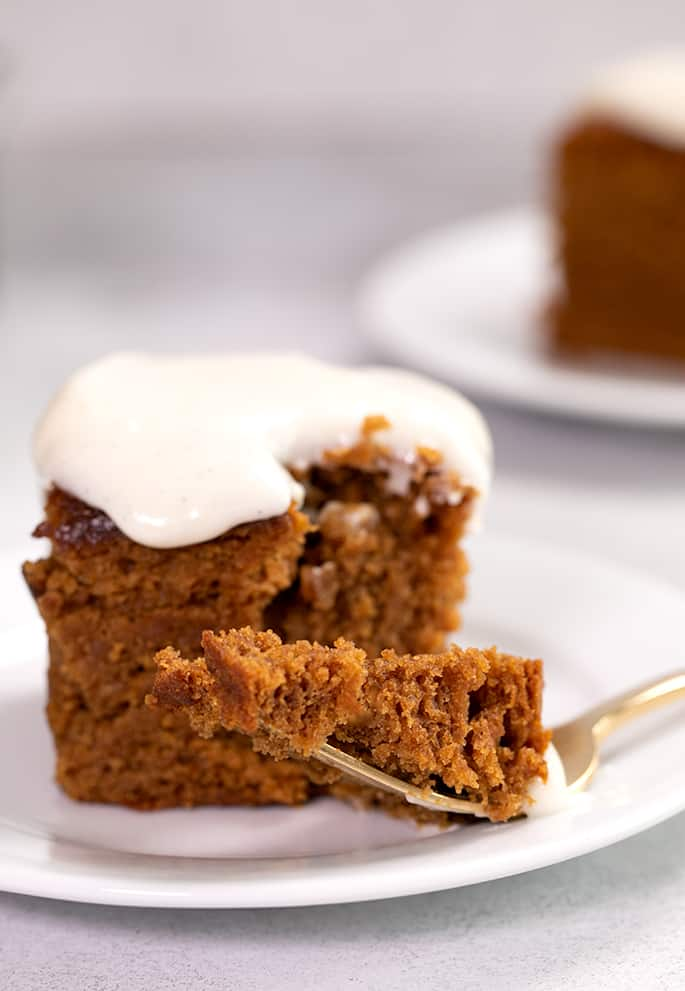 Closeup image of forkful of gingerbread cake on small white plate