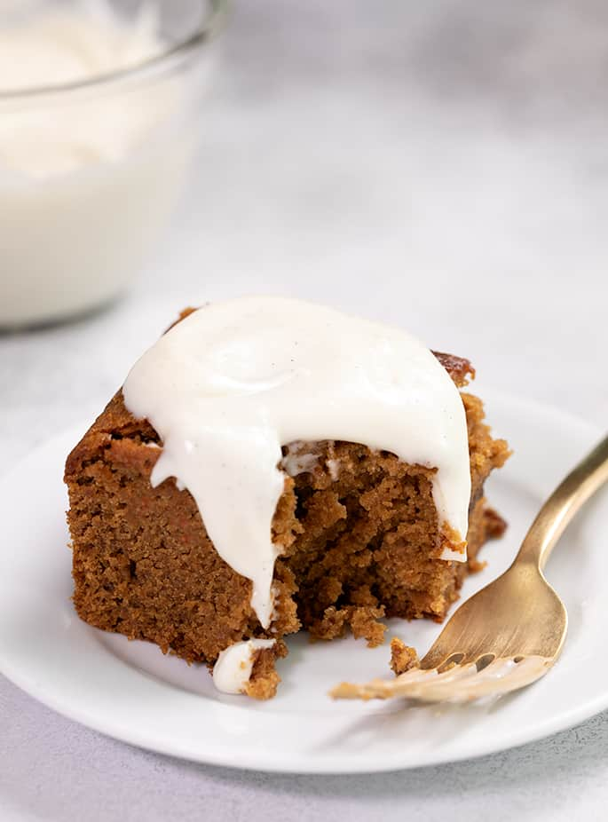 Gingerbread cake with white frosting on small white plate with fork and bite taken