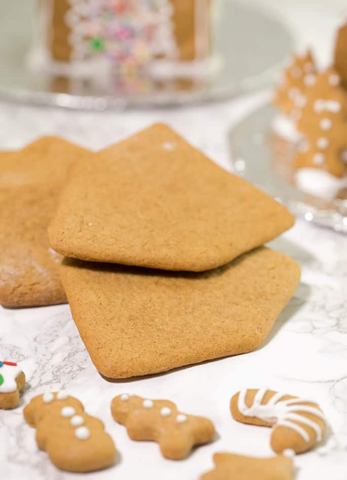 3 house shaped gingerbread cookies on marble surface