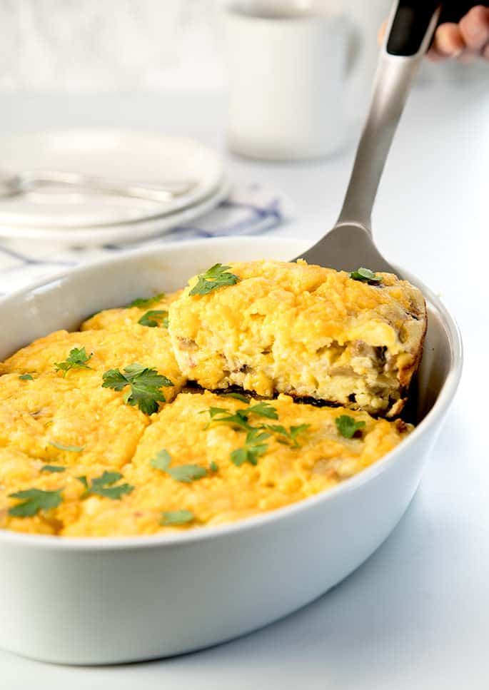 A platter of breakfast casserole with herbs on top with a piece of casserole being scooped out of the dish with a spatula.