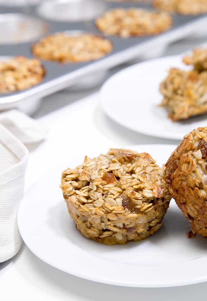 An oatmeal muffin with another oatmeal muffin leaning against it on a white plate with another plate of oatmeal muffins and a tray of oatmeal muffins in background