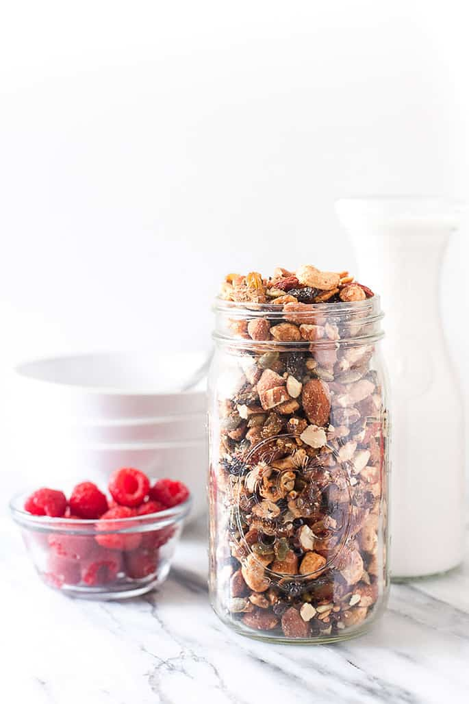 A jar of granola, and white bottle, white bowls and a bowl of raspberries on a white background