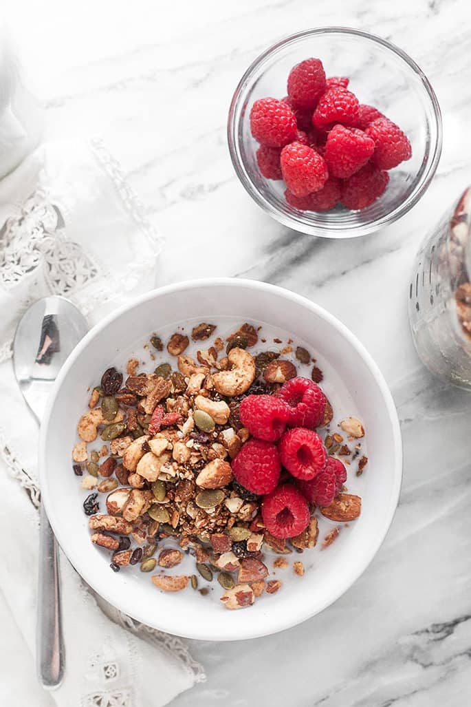 A bowl of granola with milk and raspberries with a spoon and a white cloth on a marble counter with a bowl of raspberries and jar of granola in background