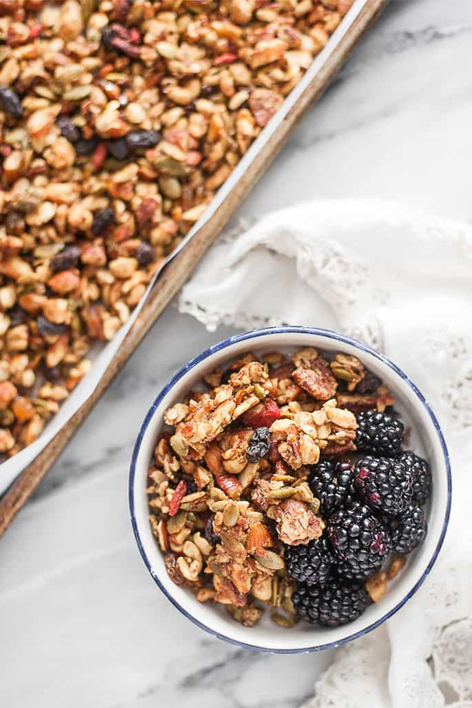 A bowl of granola with blackberries on a marble tabletop with white cloth on it and a tray of granola in corner of image