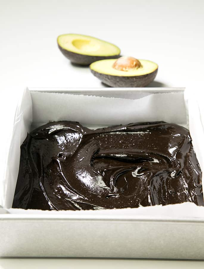A baking dish of avocado brownie batter and an avocado on white background