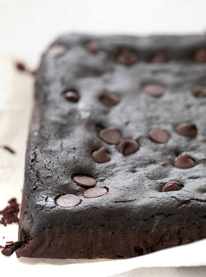 Black bean brownies out of pan uncut on white paper