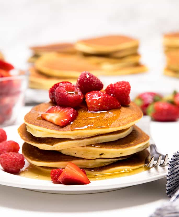 A stack of coconut flour pancakes with honey and fruit on a plate