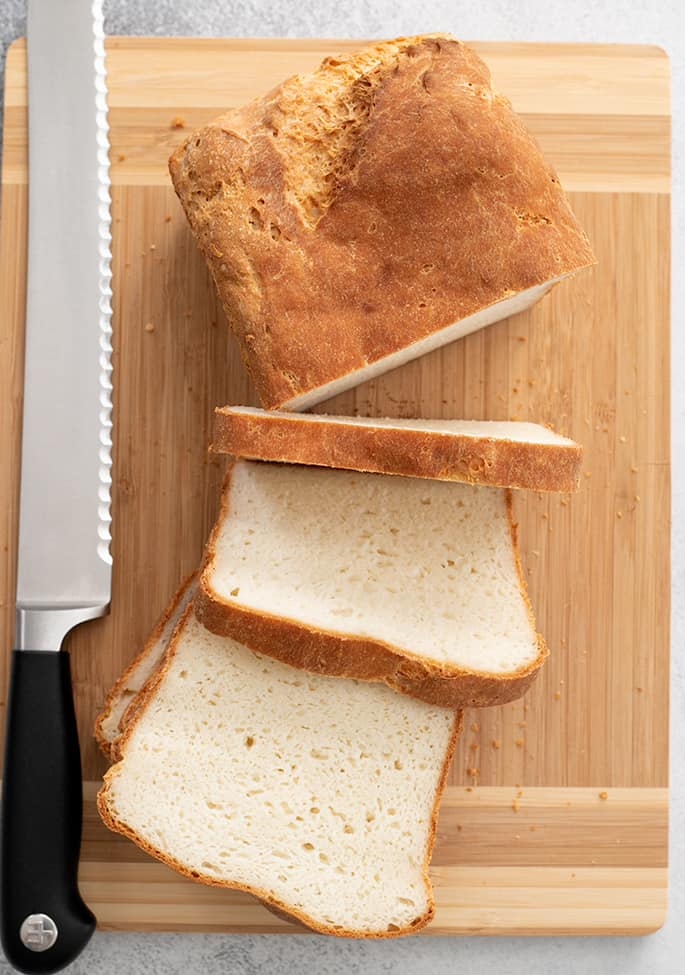 English muffin bread loaf partially sliced on a cutting board overhead image