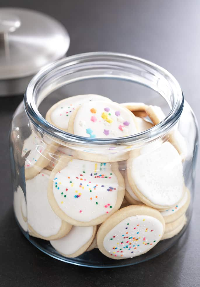 Gluten free soft cutout sugar cookies with royal icing, stored in a large glass jar.