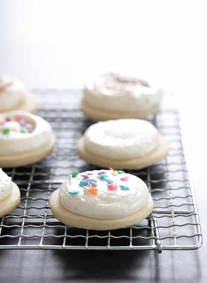 Gluten free soft frosted sugar cookies decorated with sprinkles, sitting on rack