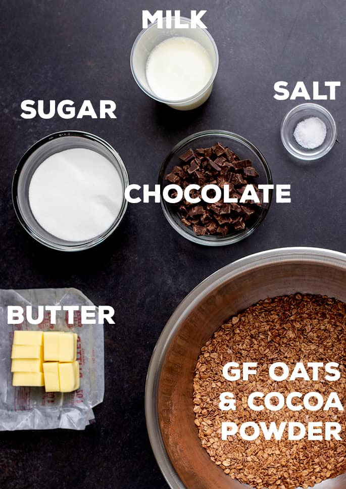 Sugar, milk, salt, chocolate, butter, gf oats and cocoa powder on black table