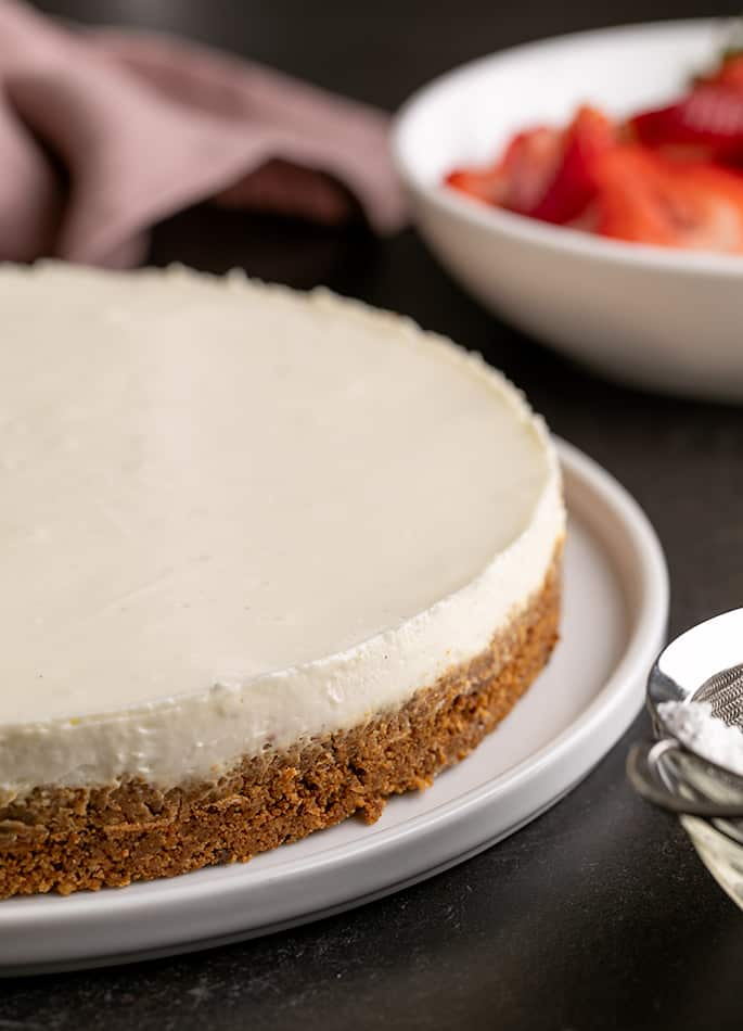 Whole cheesecake with cookie crust from side with sliced strawberries in white bowl in background