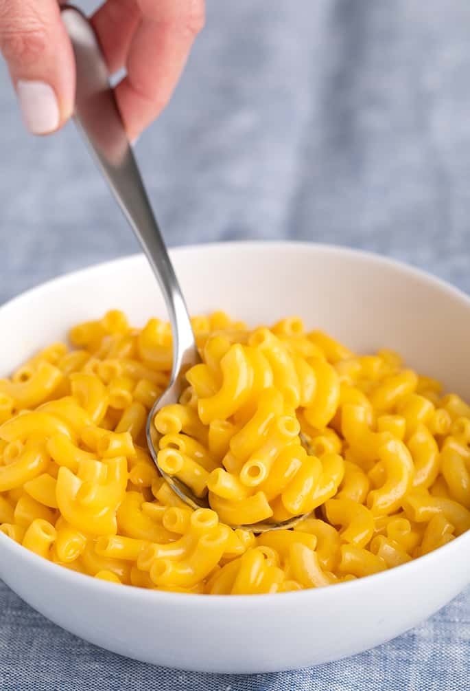 Fingers holding spoon taking a spoonful of elbow macaroni in cheese sauce in white bowl on blue cloth