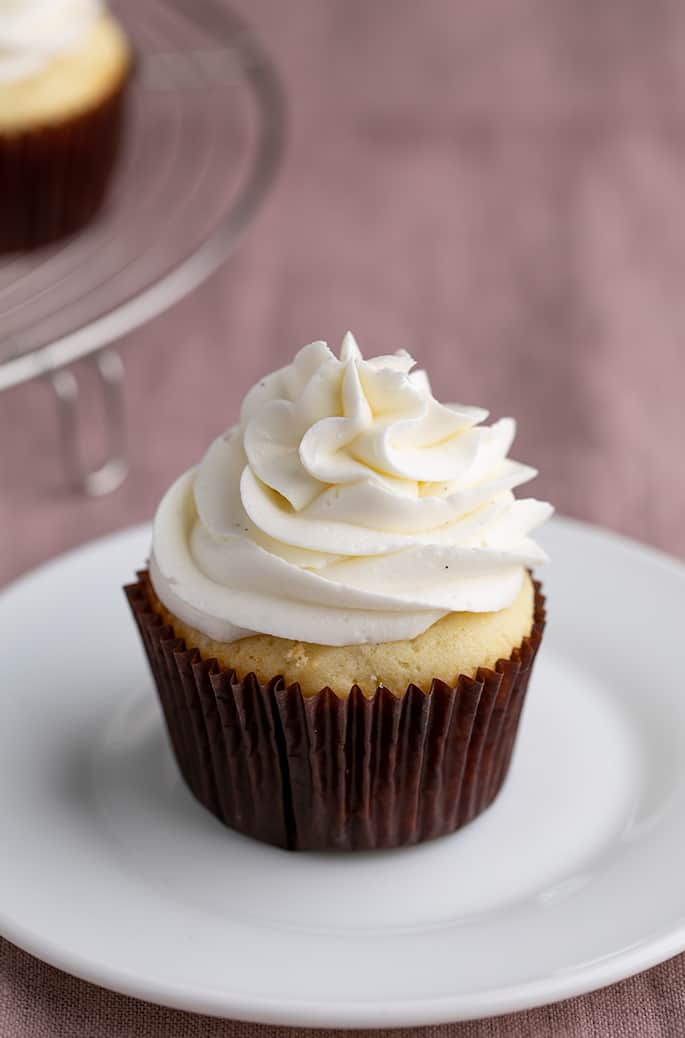 Vanilla cupcake in brown liner with white swirl of frosting on small white plate on purple cloth