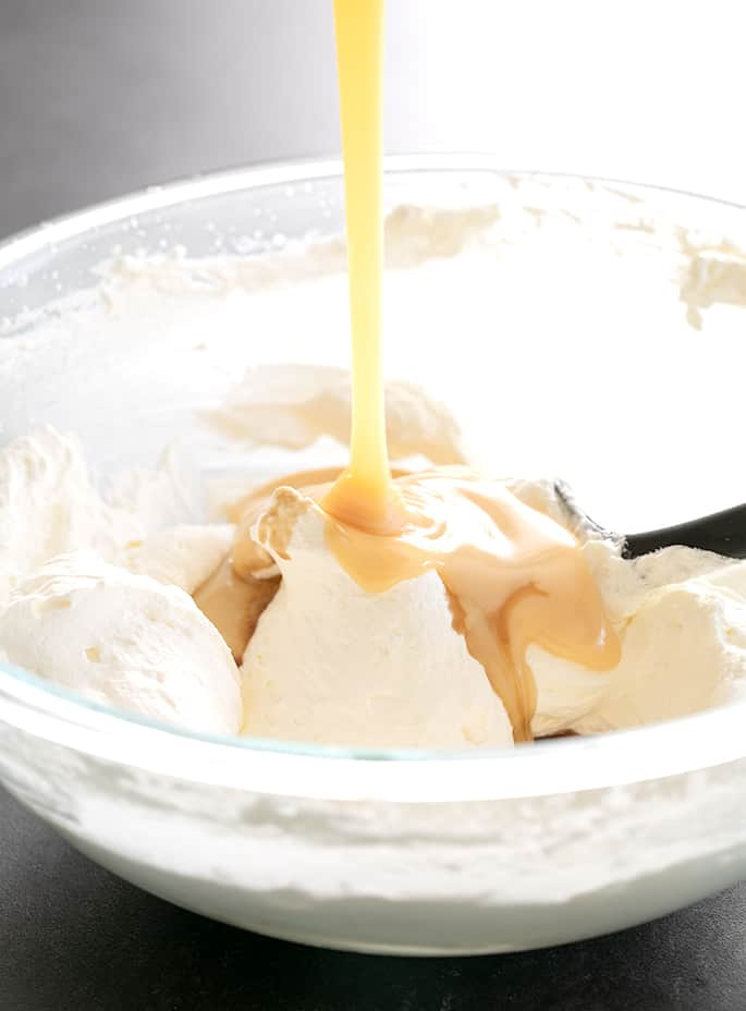 Pouring condensed milk into whipped cream